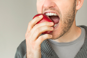 Closeup of man with beard biting an apple